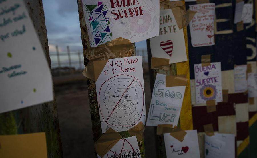 Papéis com mensagens de boa sorte para os migrantes são colado na cerca da fronteira entre os EUA e México em Playas de Tijuana, estado da Baixa Califórnia, México