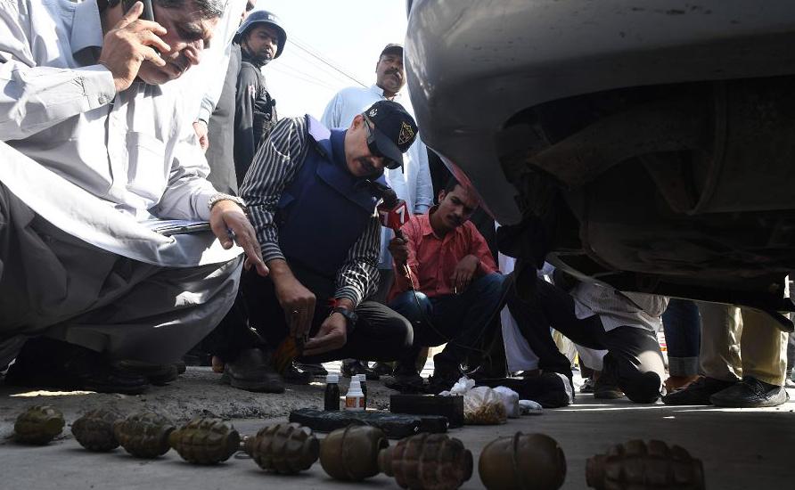 Investigadores paquistaneses vistoriam a área do Consulado Chinês após um ataque em Karachi quando dois policiais foram mortos por pistoleiros não identificados.
