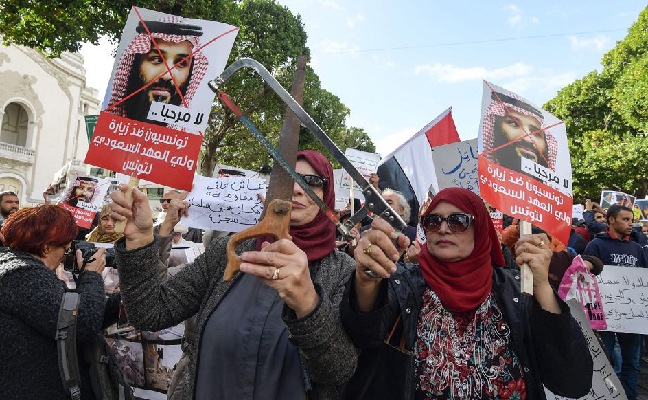 Tunisianas mostram serras e fotos do príncipe saudita Mohammed bin Salman, protestando contra sua visita ao país.