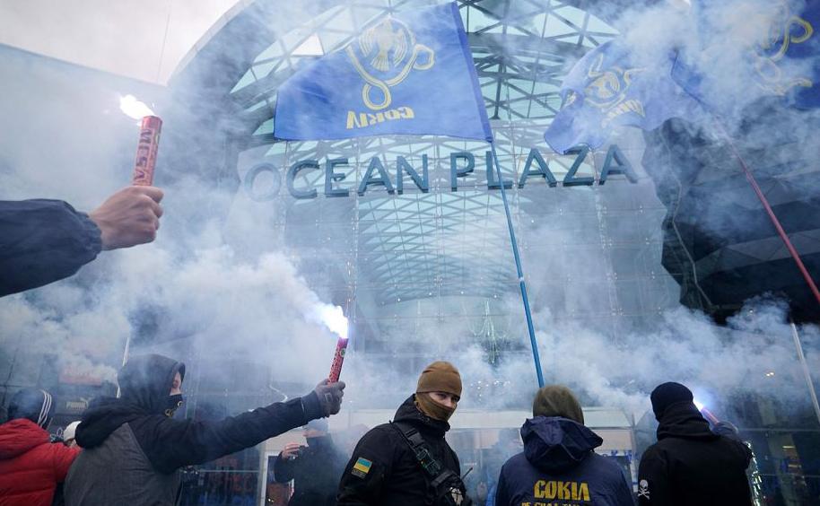 Ativistas de extrema-direita ucraniana acendem morteiros na porta do shopping center Ocean Plaza em Kiev, pertencente ao pertencente ao oligarca russo Boris Rotenberg.
