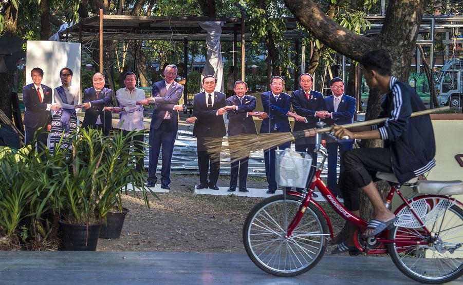 Ciclista passa ao largo dos retratos em tamanho natural dos 10 líderes da Associação de Nações do Sudeste Asiático (ASEAN).