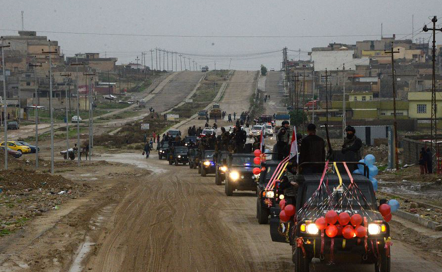 Desfile militar nas ruas da cidade iraquiana de Mosul, durante as celebrações que marcam o primeiro aniversário da vitória do país sobre o estado islâmico (IS),
