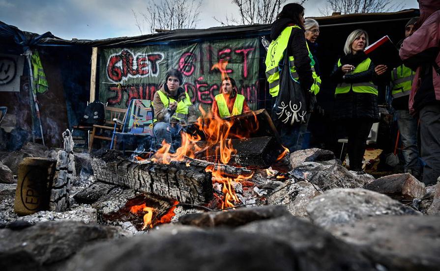 Manifestantes de colete amarelo (Gilets jaunes) ocupam parte da estrada em Saint-Etienne. O Presidente francês defendeu um pacote de socorro financeiro para reprimir a revolta sobre os impostos.