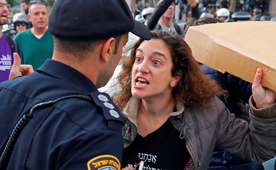 Mulheres israelenses enfrentam a polícia durante uma manifestação contra a violência  doméstica na cidade costeira mediterrânica de Tel Aviv.