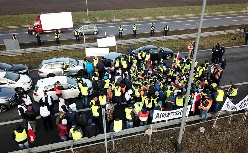 Agricultores poloneses vestidos como os manifestantes franceses de coletes amarelos bloqueiam uma auto-estrada no sentido de Varsóvia, para exigir do governo apoio aos  fazendeiros que sofrem com  o surto da peste suína.