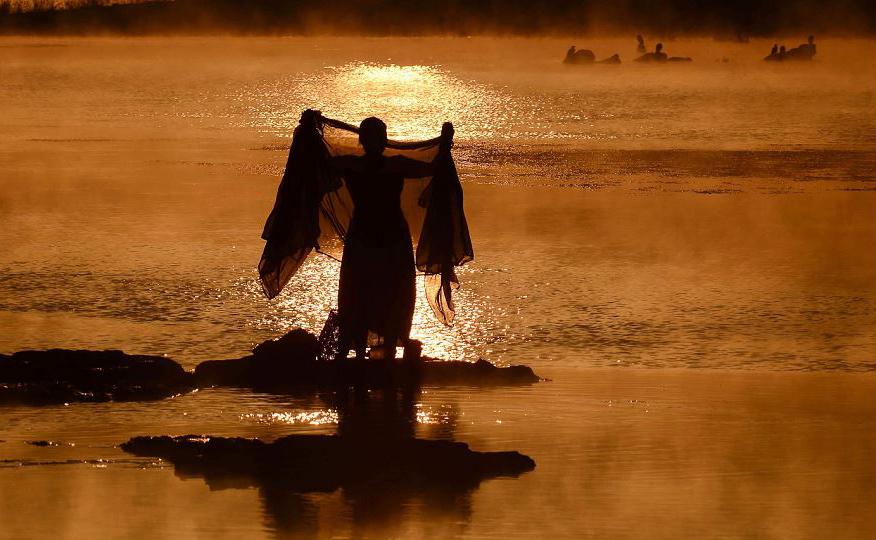 Indiana lava um sari no Rio Narmada ao nascer do sol numa manhã de inverno nevoento em Jabalpur, no estado de Madhya Pradesh