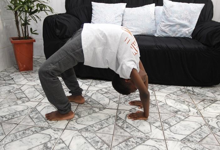 Garoto mostra flexibilidade na sala de casa