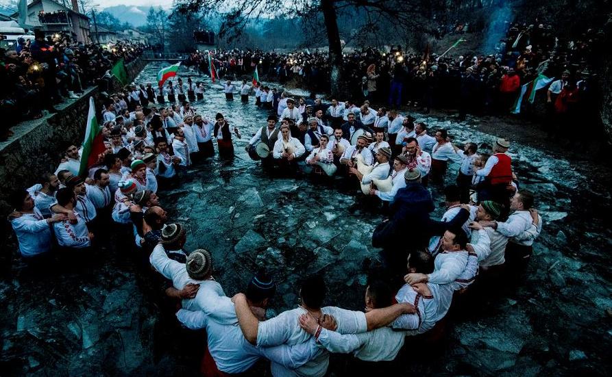 """Búlgaros fazem a tradicional dança de """"Horo"""" nas águas geladas do rio Tundzha na cidade de Kalofer, parte das comemorações do dia da Epifania. Um padre ortodoxo lança uma cruz no rio e acredita-se que quem  a recuperar será saudável."""