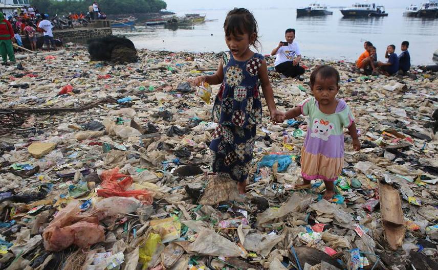Crianças ajudam a limpar o lixo da Baía de Lampung, na aldeia de Sukaraja um subdistrito de  Bumi Waras em Bandar Lampung. Funcionários do governo, moradores e a polícia tomam parte no evento anual.