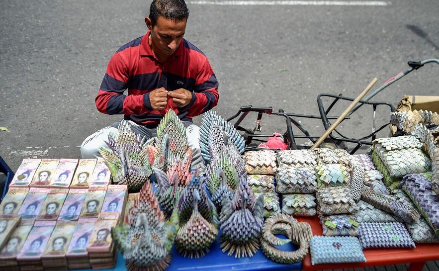 Um homem vende artesanatos feitos com notas de Bolívar em uma rua de Cúcuta, Colômbia, na fronteira com a Venezuela. O peso colombiano sobrepôs o desvalorizado Bolívar venezuelano em cidades fronteiriças, no epicentro de uma crise política.