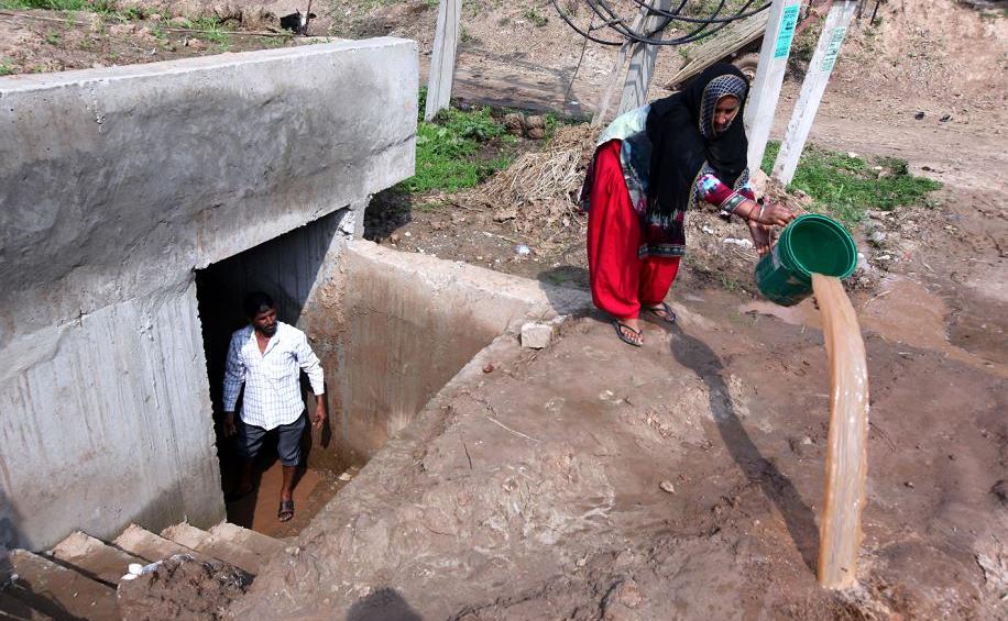 Aldeões indianos da fronteira Índia-Paquistão removem água de um bunker perto de Jammu, na  Caxemira.