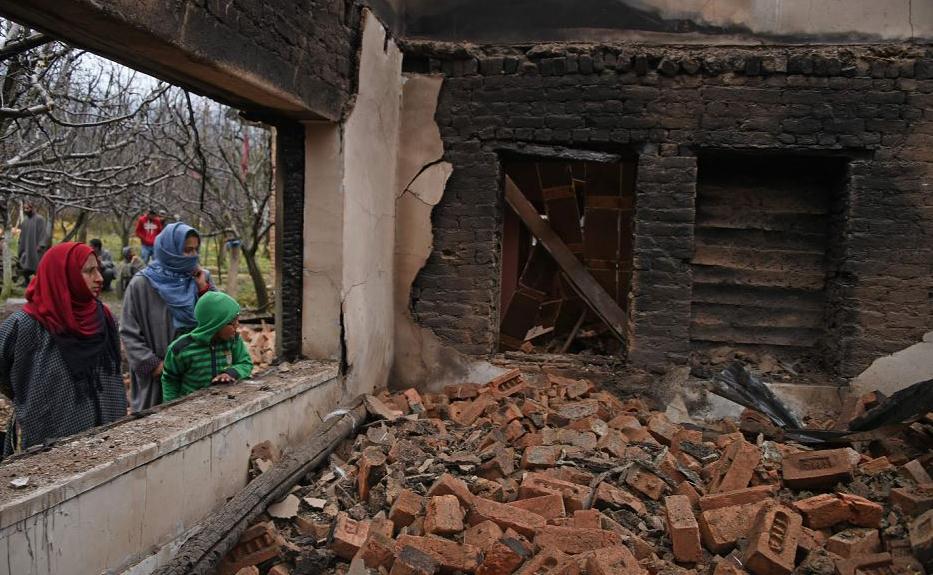 Aldeãs da Caxemira olham os restos de uma casa destruída durante uma batalha mortal entre militantes e as forças do governo indiano na área de Pinglish de Tral, no distrito de Pulwama, ao sul de Srinagar.