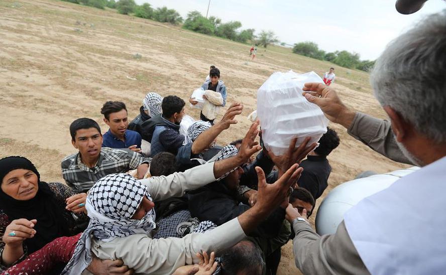 Iranianos recebem ajuda do Crescente Vermelho na aldeia de Susangerd, na província do Khuzistão, após o país ser atingido por várias semanas de inundações sem precedentes que já matou 70 pessoas.