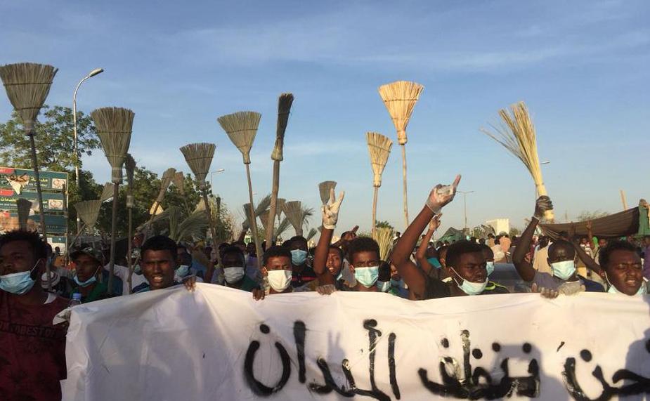 Sudaneses protestam com vassoras, a favor da queda do governo,  em frente ao quartel-general militar na capital, Khartoum.