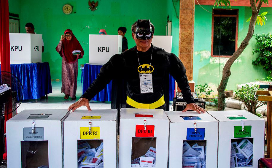 Mesários da Indonésia se veste de super-heróis num local de voto em Surabaya.