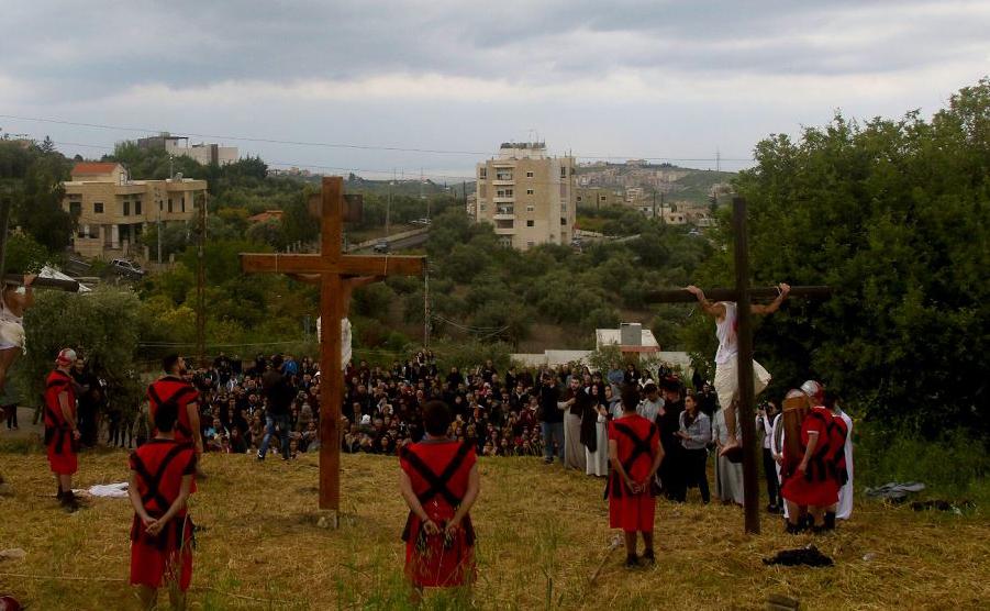 Cristãos libaneses são amarrados a uma cruz de madeira na reencenação da crucificação de Jesus Cristo, durante as celebrações de sexta-feira no sul da vila libanesa de al-Qurayeh, perto da cidade de Sidon.