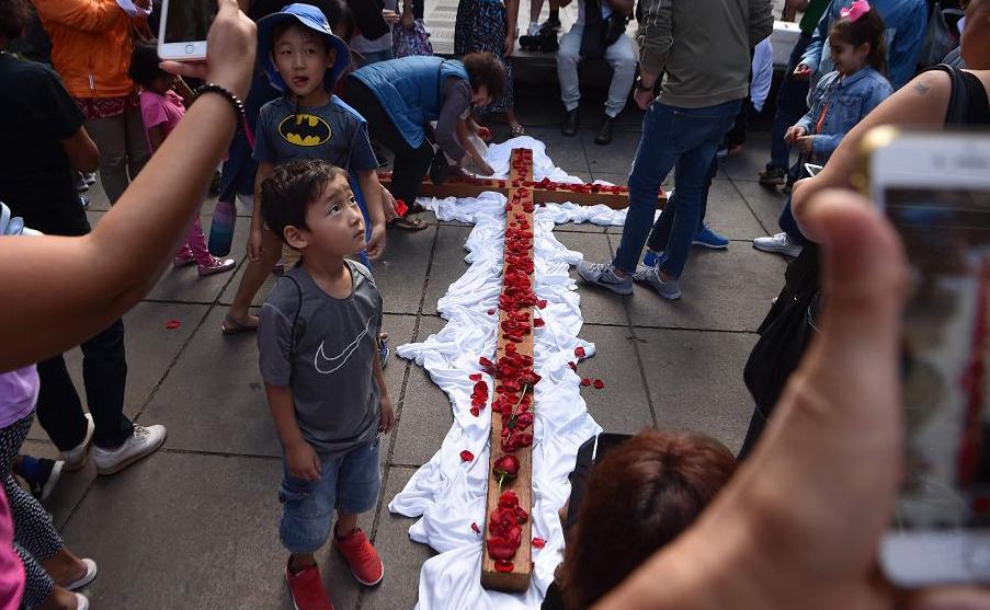 Devotos colocam pétalas de rosa numa cruz após a reencenação da crucificação de Jesus Cristo na sexta-feira, em Sydney