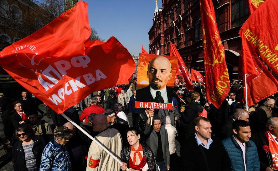 Partidários e membros do Partido Comunista russo caminham para o Mausoléu do fundador do estado soviético e líder revolucionário Vladimir Ilyich Ulyanov, Lenin para colocar flores na Praça Vermelha de Moscou.