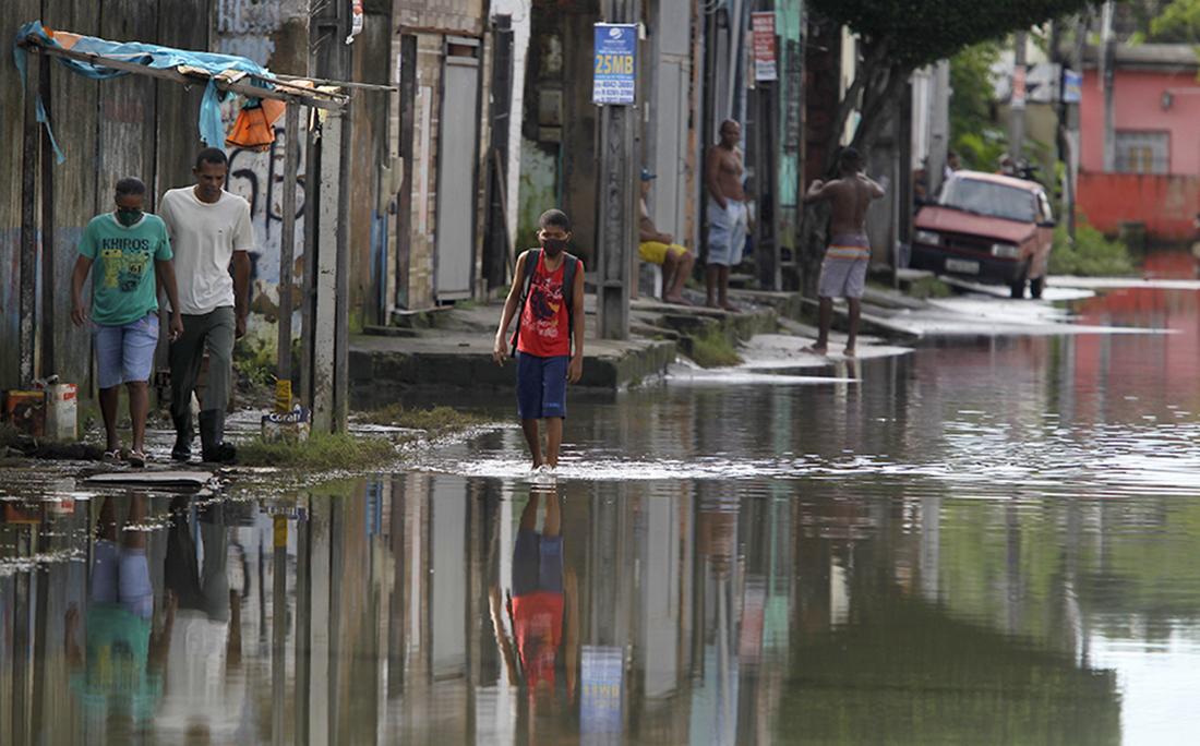 Homem caminha em rua alagada de São Cristóvão.