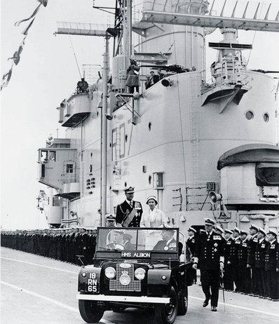 Elizabeth II em 1957 a bordo de um Land Rover Series I, o precursor do Defender