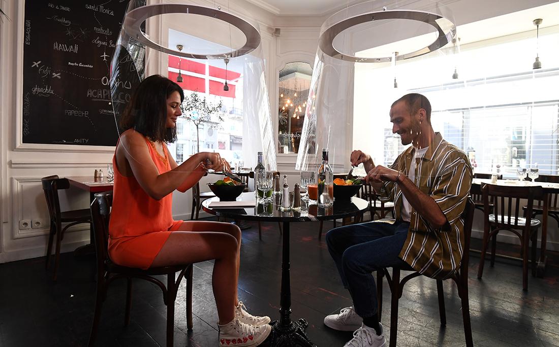 Um casal almoça sob equipamento projetado por Christophe Gernigon em restaurante de Paris, na França.