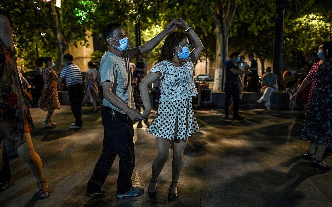 Pessoas dançam usando máscara em um parque próximo ao rio Yangtze, em Wuhan, cidade chinesa onde o coronavírus foi registrado pela primeira vez.