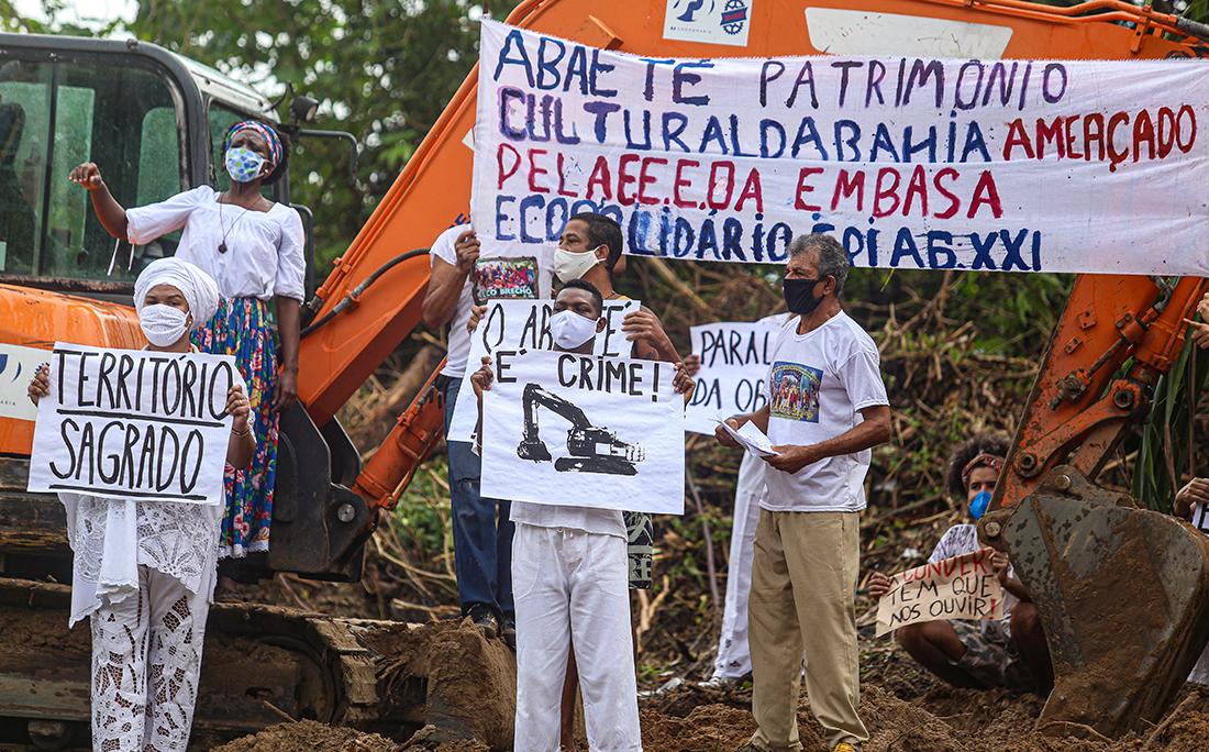 Manifestantes exibiam cartazes pedindo a paralisação da obra, respeito à cultura local e ao povo de matriz africana, que tem a lagoa um local sagrado.