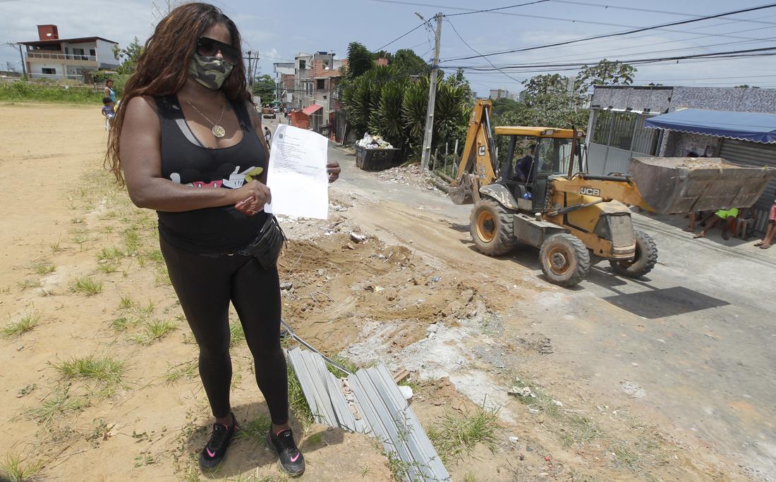 A dona do imóvel, Araci dos Reis, 29 anos, mostra a liminar da Defensoria Pública do Estado (DPE), documento que concedeu a tutela provisória do imóvel.